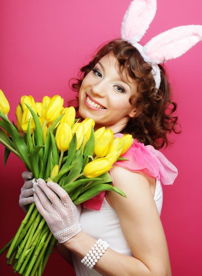 Vrouw met Bunny Ears dat gele tulpen houdt stock afbeeldingen