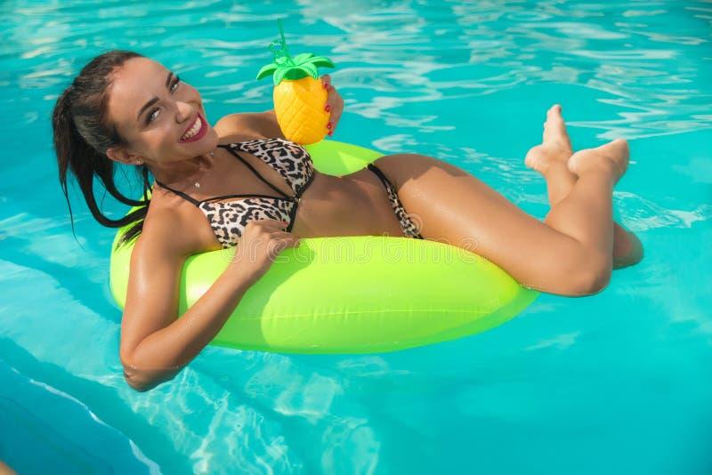 Vrouw met cocktail in de pool stock afbeeldingen