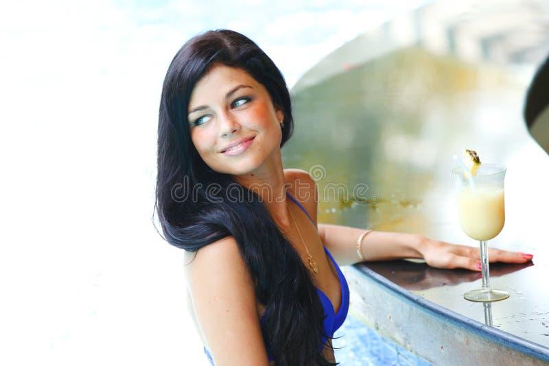 Vrouw met cocktail in zwembad stock afbeeldingen
