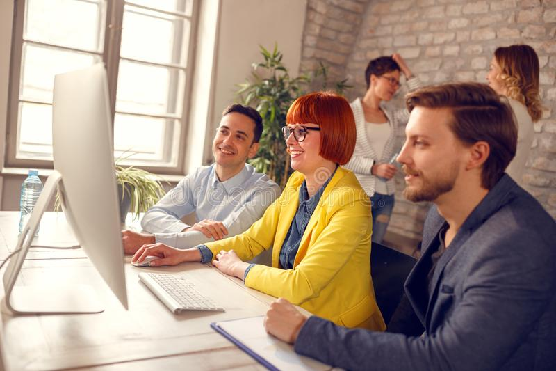 Vrouw met collega's bij werkplaats op computer royalty-vrije stock fotografie