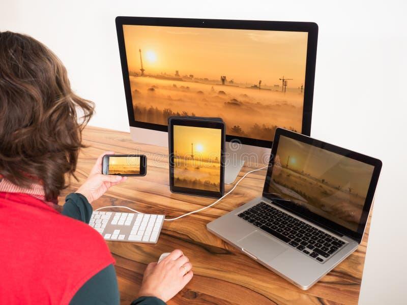 Vrouw met computers en mobiele apparaten stock afbeelding
