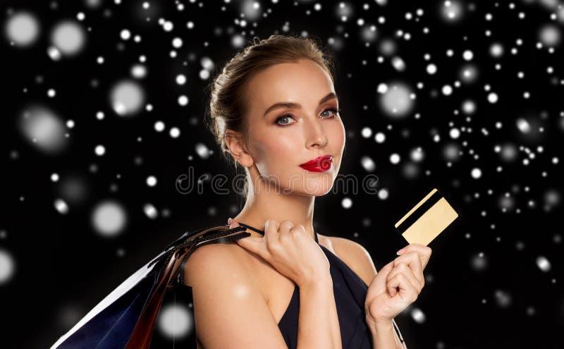 Vrouw met creditcard en het winkelen zakken over sneeuw stock afbeeldingen