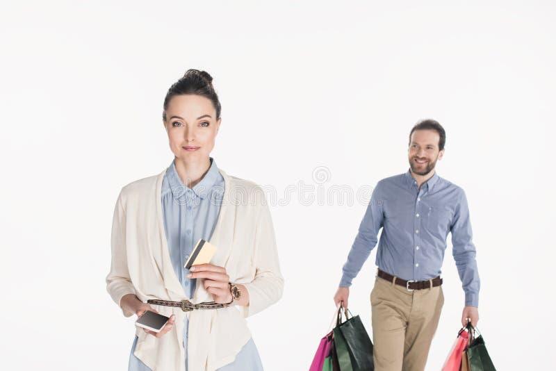 vrouw met creditcard en smartphone die camera bekijken terwijl echtgenoot dragen die in zakken doet winkelen stock afbeelding