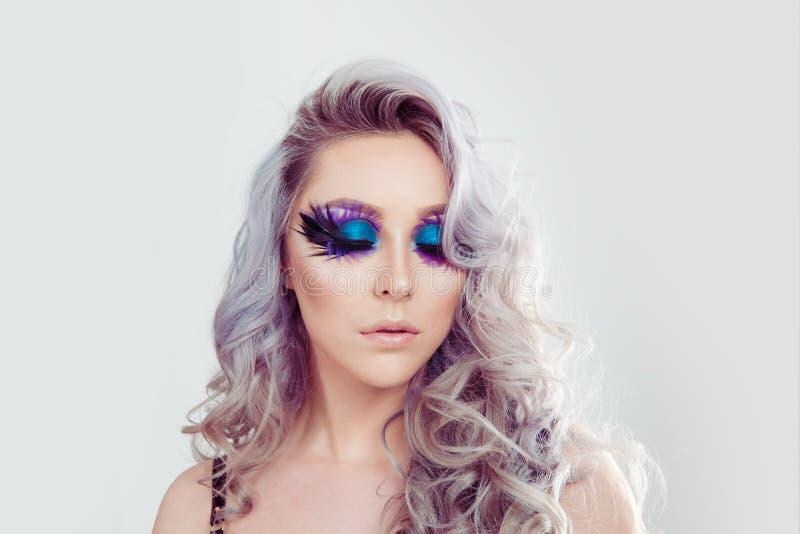 Vrouw met de artistieke purpere blauwe veer van de ogenmake-up op wimpers stock afbeelding