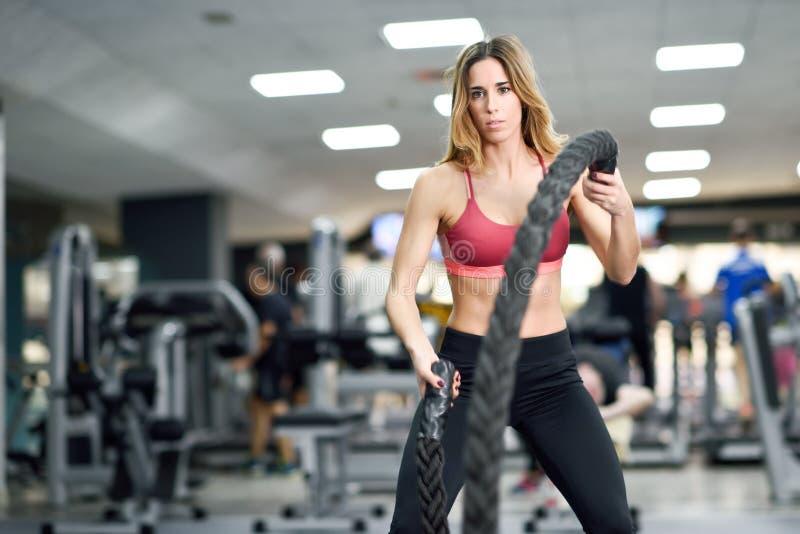Vrouw met de oefening van slagkabels in de geschiktheidsgymnastiek stock afbeelding