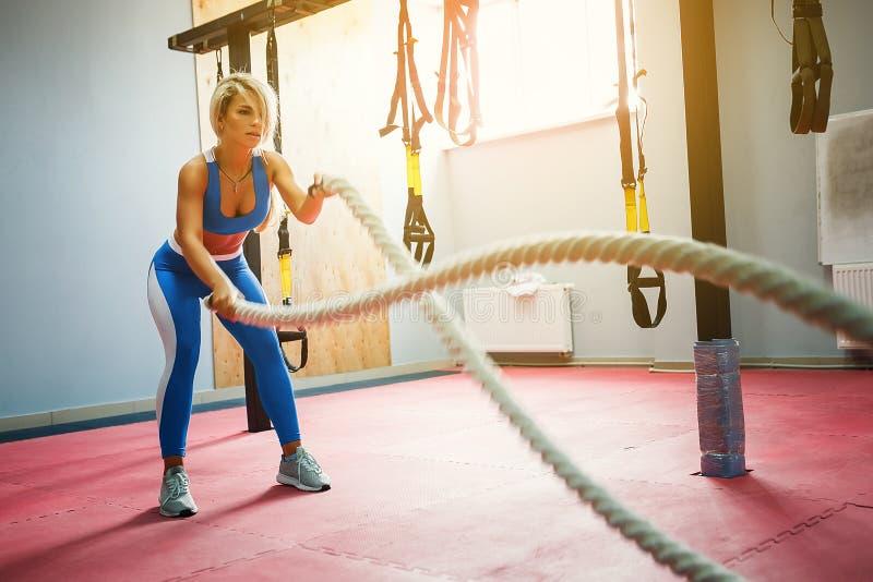 Vrouw met de oefening van slagkabels in de geschiktheidsgymnastiek Jonge vrouwelijke dragende sportkleding royalty-vrije stock fotografie