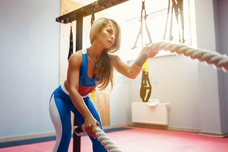 Vrouw met de oefening van slagkabels in de geschiktheidsgymnastiek Jonge vrouwelijke dragende sportkleding stock afbeeldingen