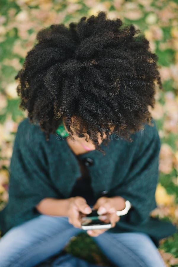 Vrouw met de stijl van het afrohaar het texting op smartphone stock foto