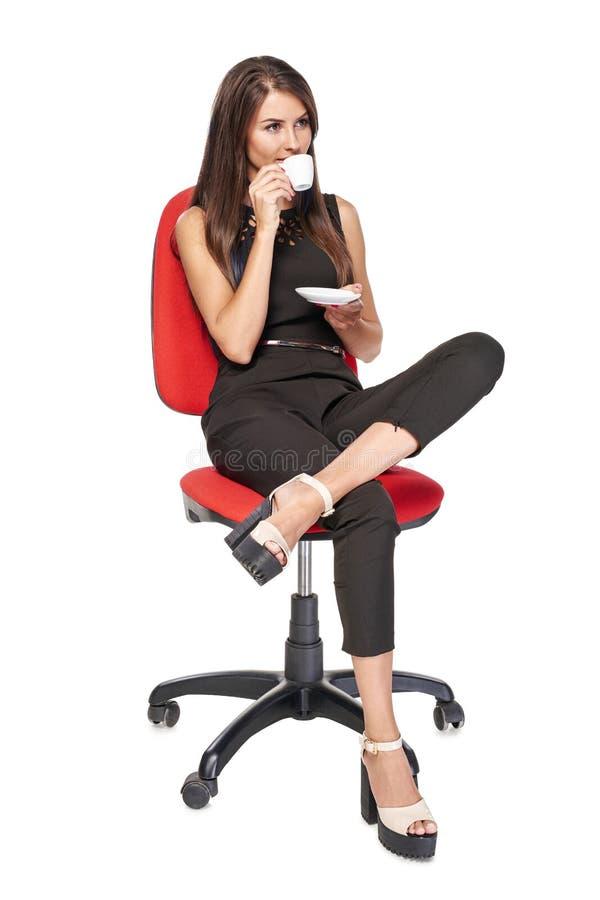 Vrouw met de zitting van de koffiekop als bureauvoorzitter royalty-vrije stock fotografie