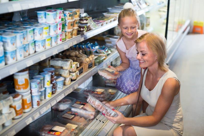 Vrouw met dochter het kopen vlees in opslag stock afbeelding