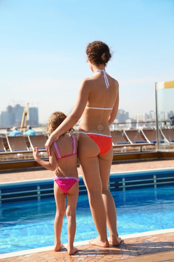 Vrouw met dochter status dichtbij zwembad royalty-vrije stock afbeelding