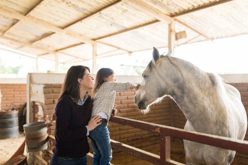 Vrouw met Dochter wat betreft Paard in Schuur stock foto's