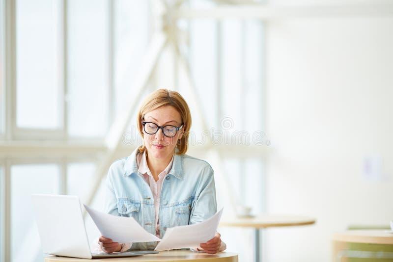 Vrouw met documenten en laptop stock foto