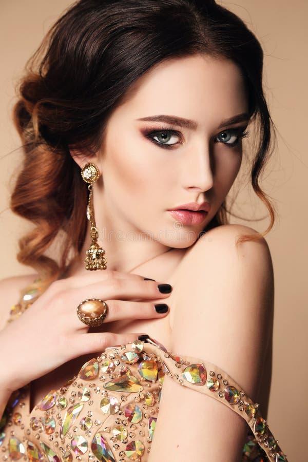 Vrouw met donker haar die luxueuze lovertjekleding en juweel dragen royalty-vrije stock foto