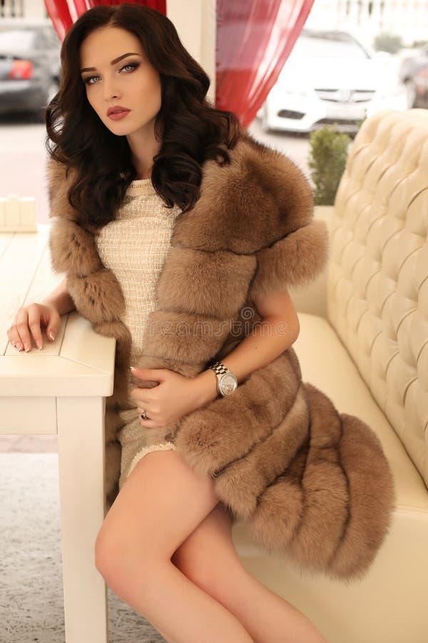 Vrouw met donker haar in elegante kleren en luxueuze bontjas royalty-vrije stock foto