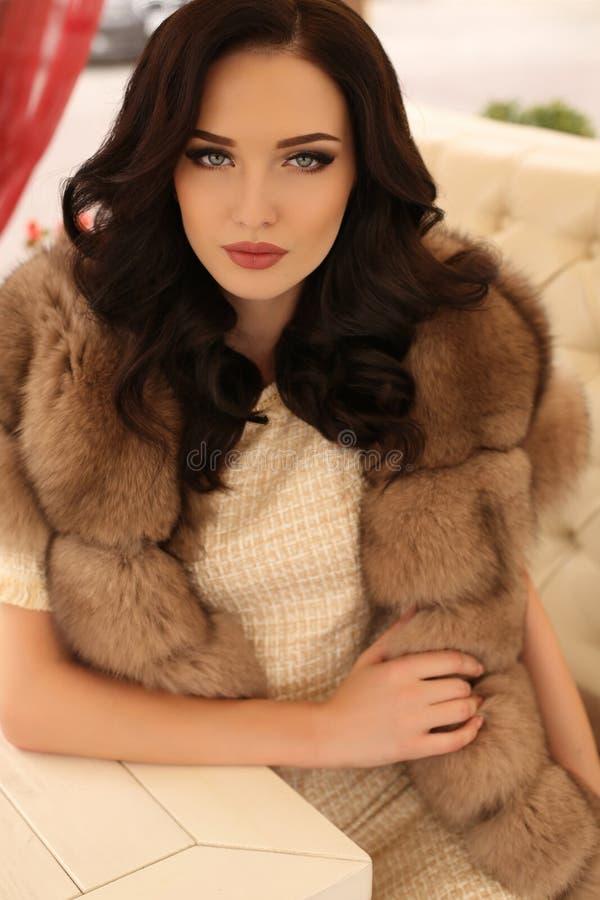 Vrouw met donker haar in elegante kleren en luxueuze bontjas royalty-vrije stock foto's