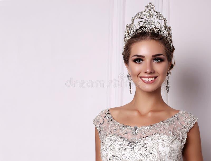 Vrouw met donker haar in luxueuze huwelijkskleding en kostbare kroon royalty-vrije stock afbeeldingen