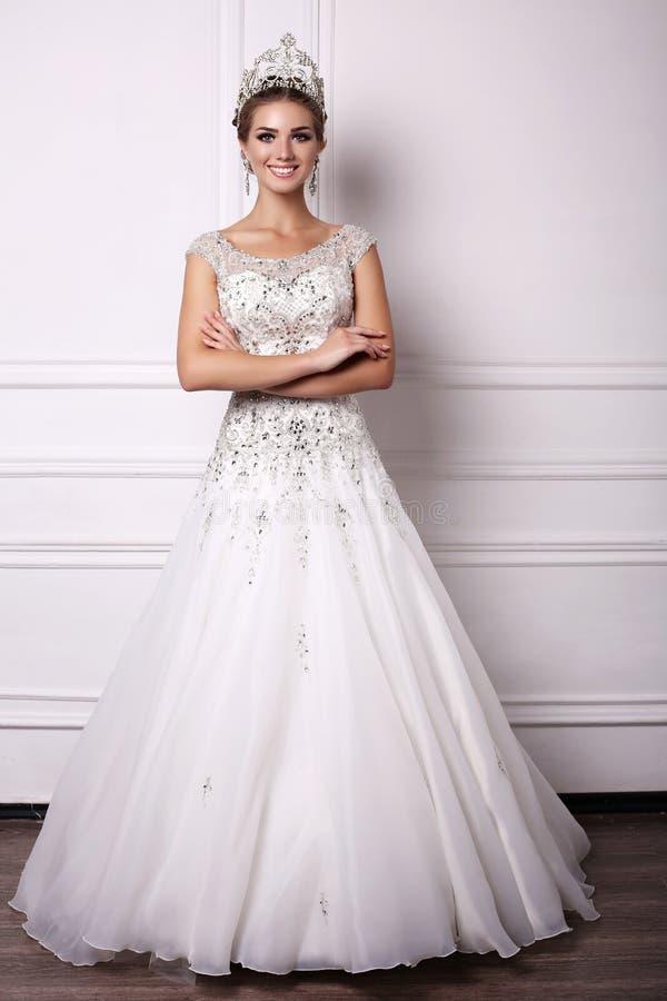 Vrouw met donker haar in luxueuze huwelijkskleding en kostbare kroon stock foto's
