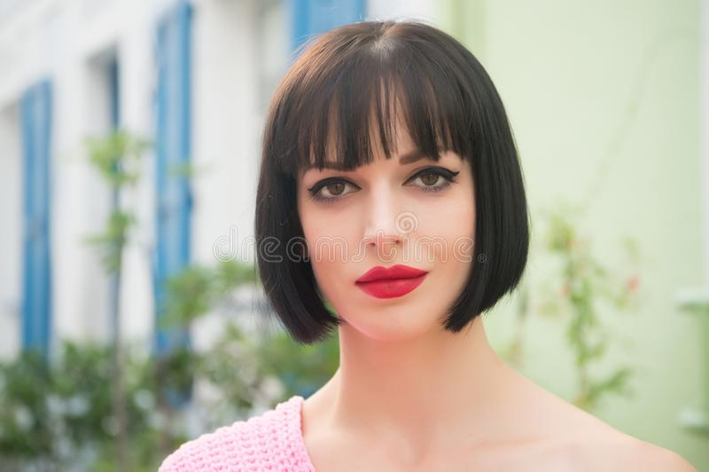 Vrouw met donkerbruin haar, rode lippen, make-upgezicht in Parijs stock foto