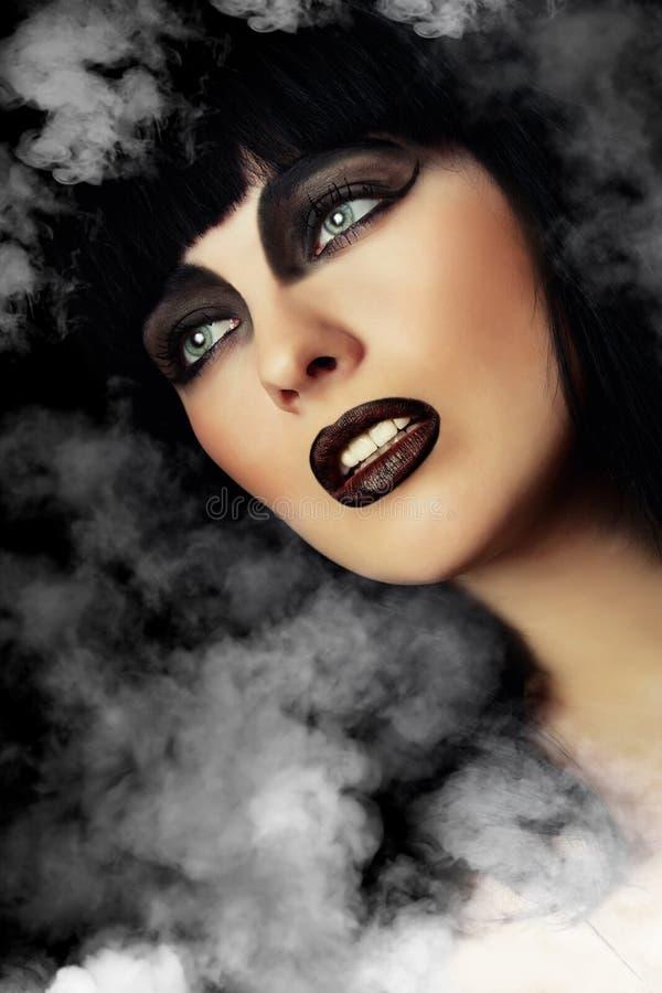 Vrouw met donkere samenstelling in een rook royalty-vrije stock afbeelding