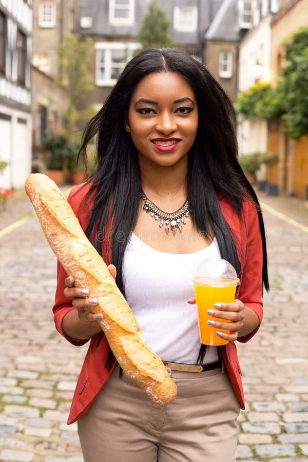 Vrouw met drank en brood stock afbeelding