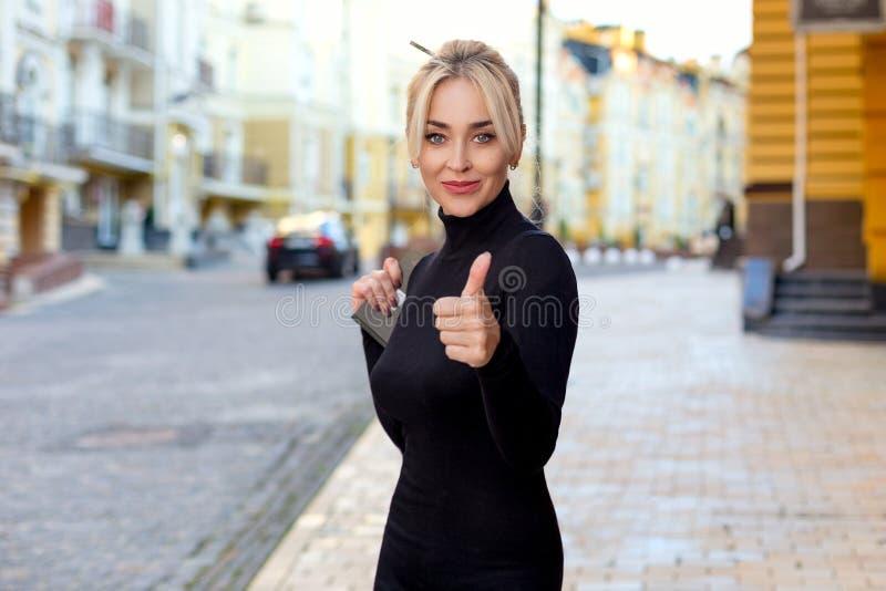 Vrouw met duim omhoog op de straat stock foto