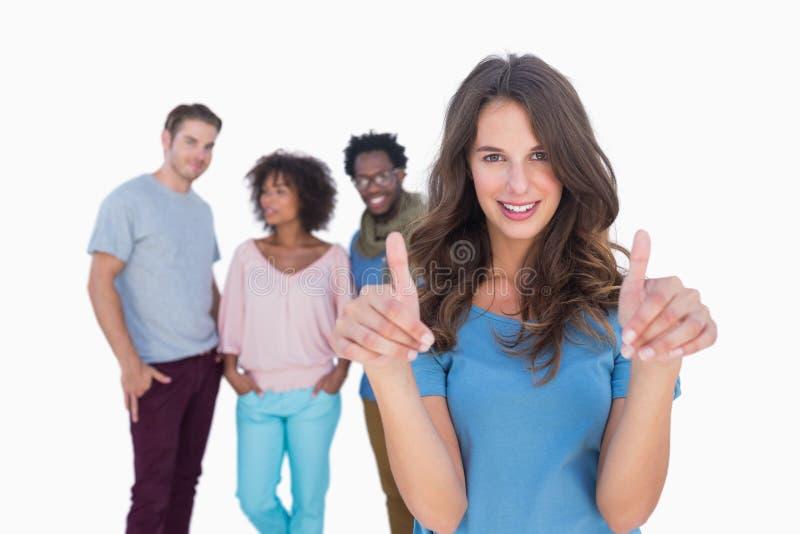 Vrouw met duimen die zich voor modieuze mensen bevinden stock fotografie