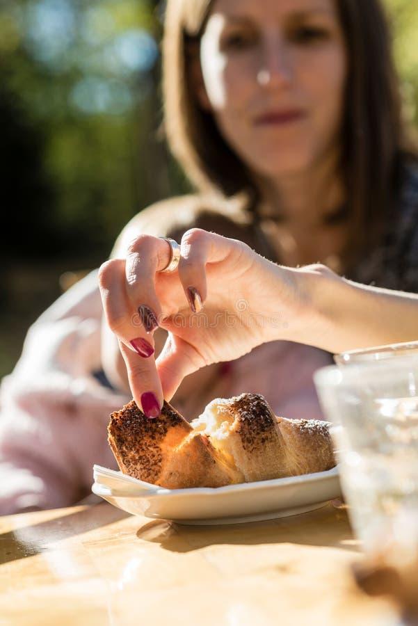 Vrouw met een baby die een stuk van croissant verwijderen uit een plaat royalty-vrije stock afbeeldingen