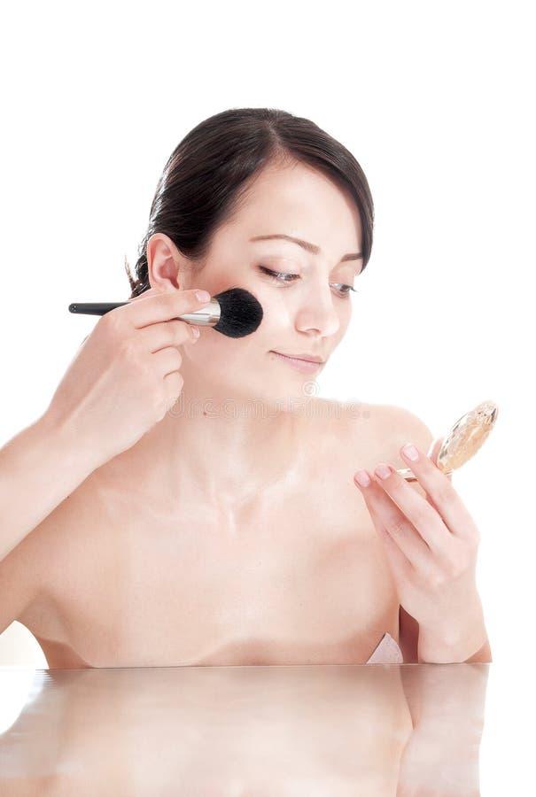 Vrouw met een borstel die in de spiegel kijken. royalty-vrije stock afbeeldingen