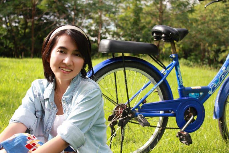 Vrouw met een fiets die in openlucht glimlacht