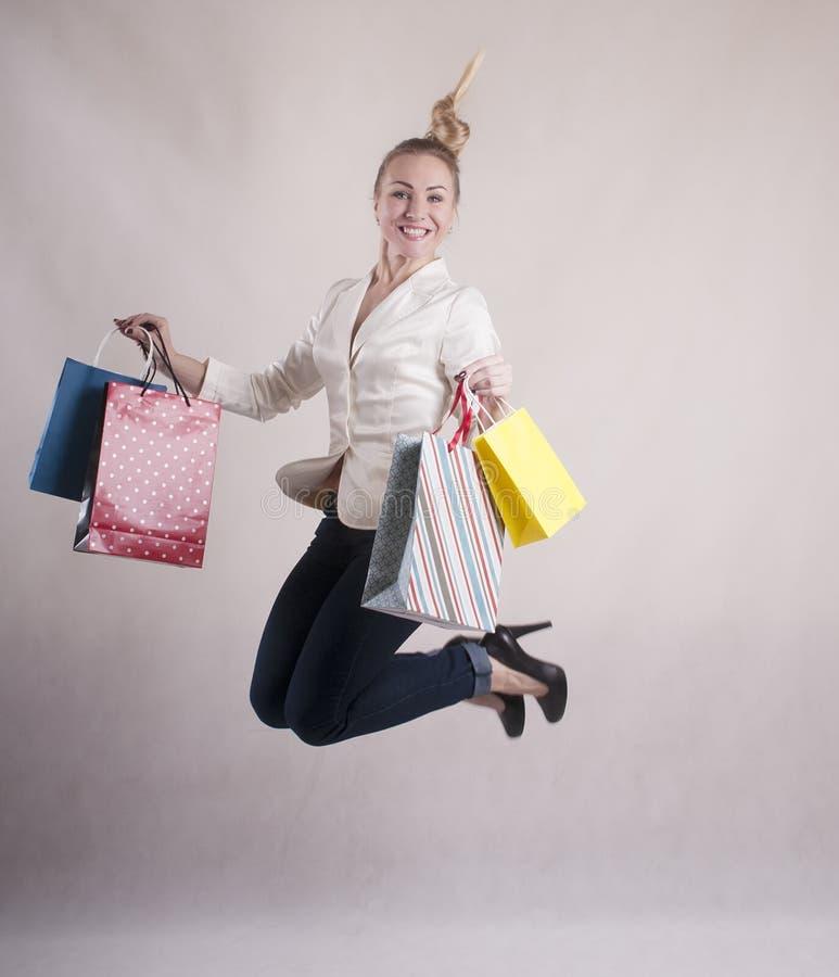 Vrouw met een geschokt die jasje in springende pakketten voor aankopenstudio wordt geschokt stock foto