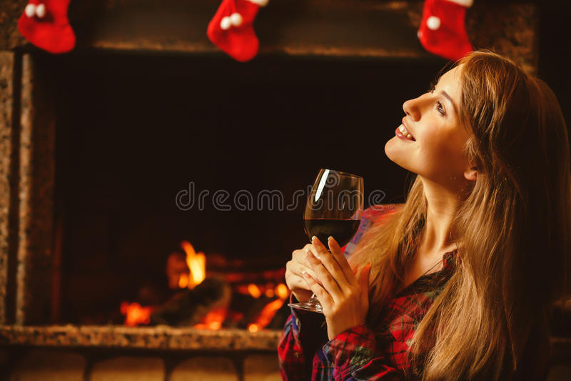Vrouw met een glas wijn door de open haard Jonge aantrekkelijke wo stock afbeeldingen
