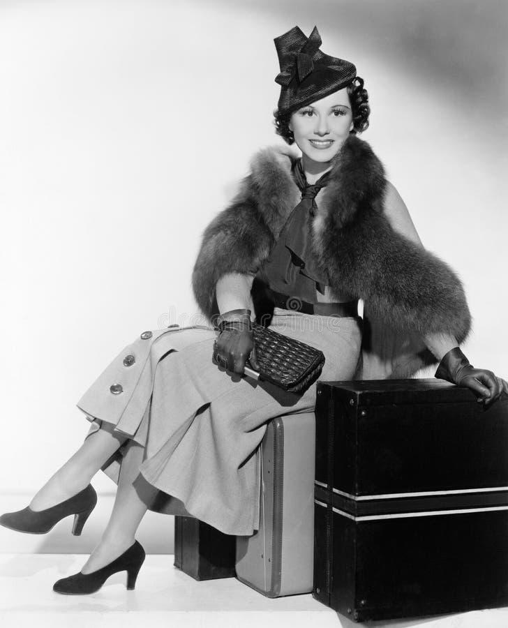 Vrouw met een hoedenzitting op koffers en het glimlachen (Alle afgeschilderde personen leven niet langer en geen landgoed bestaat stock afbeeldingen