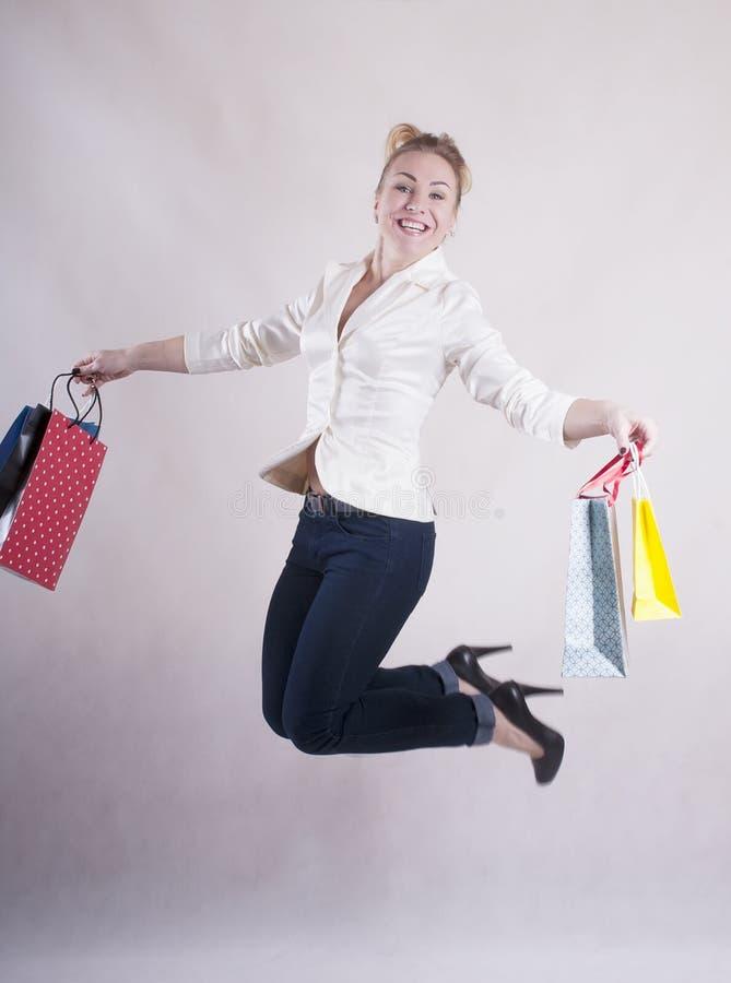 Vrouw met een jasje in springende pakketten voor aankopenstudio royalty-vrije stock fotografie