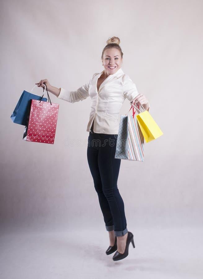 Vrouw met een jasje in springende pakketten voor aankopenstudio die wordt geschokt stock afbeelding