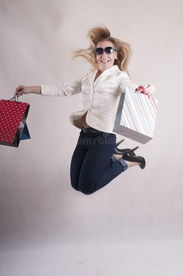 Vrouw met een jasje in zonnebril die pakketten voor aankopenstudio springen royalty-vrije stock afbeelding