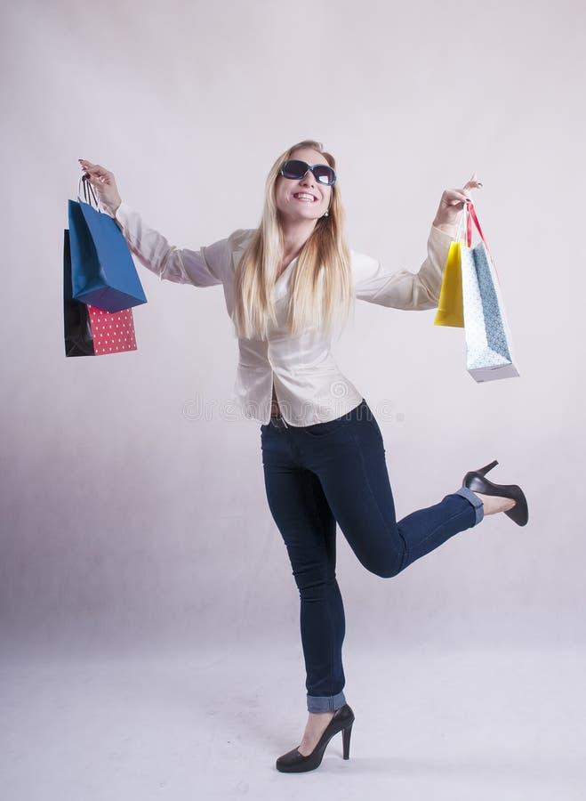 Vrouw met een jasje in zonnebrilpakketten voor aankopenstudio royalty-vrije stock afbeeldingen