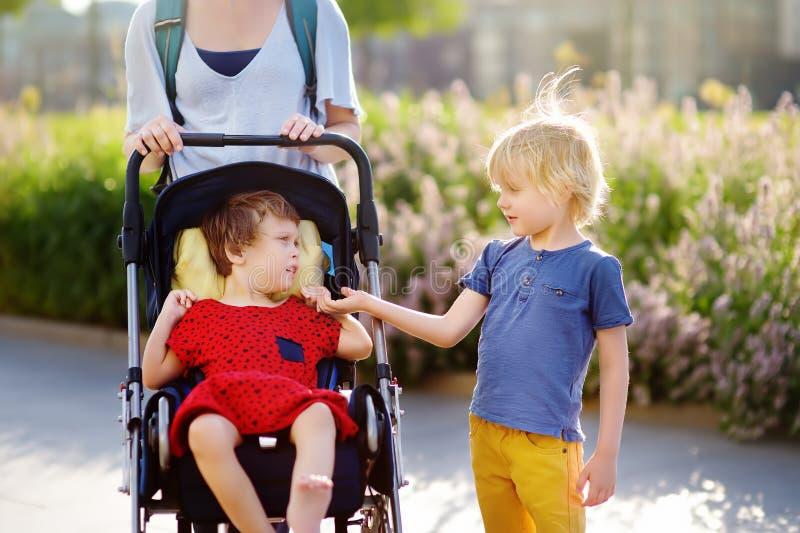 Vrouw met een jongen en een gehandicapt meisje in een rolstoel die in de Parkzomer lopen Kind hersenverlamming Familie met gehand royalty-vrije stock foto