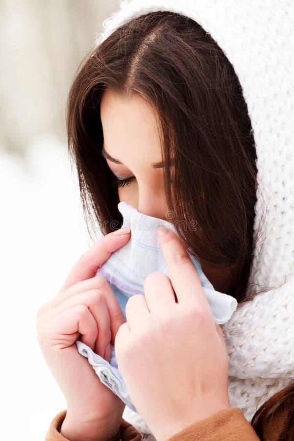 Vrouw met een koude holding een weefsel stock fotografie