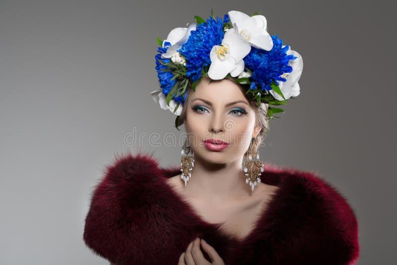 Vrouw met een kroon van bloemen op haar hoofd in een bontjas jong stock fotografie