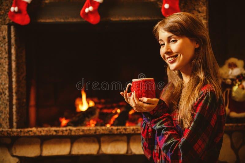 Vrouw met een mok door de open haard Jonge aantrekkelijke vrouwensittin stock foto