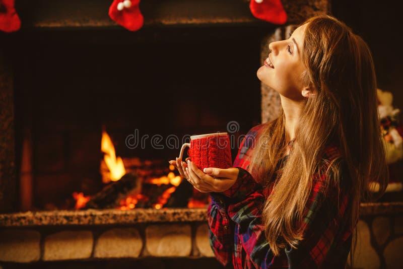 Vrouw met een mok door de open haard Jonge aantrekkelijke vrouwensittin stock fotografie