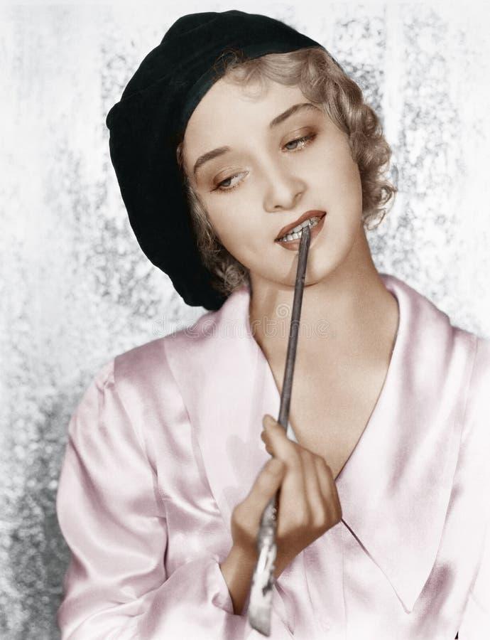 Vrouw met een penseel tussen haar tanden (Alle afgeschilderde personen leven niet langer en geen landgoed bestaat Leveranciersgar stock foto