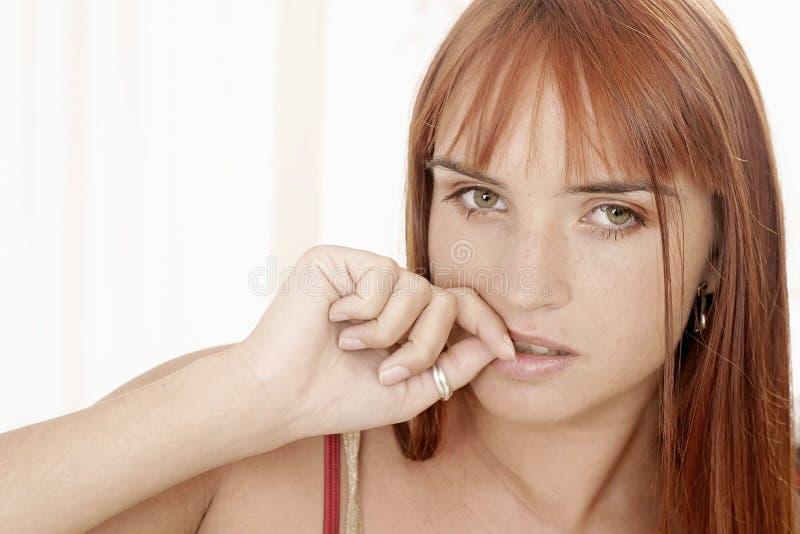 Vrouw met een rand die haar spijkers bijt stock foto's