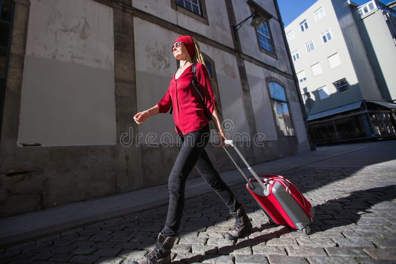 Vrouw met een rode koffer die onderaan de straat van de stad lopen Reis stock foto