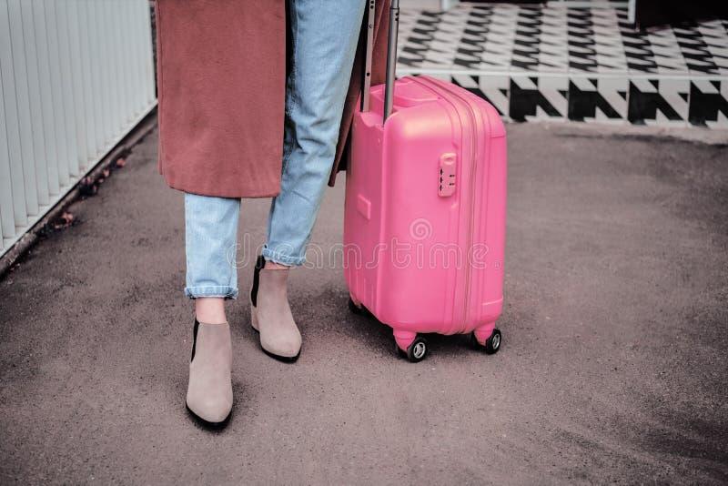 Vrouw met een roze koffer op de trein op de achtergrond van het treinstation reizen, toeristen, vakantieconcept stock fotografie
