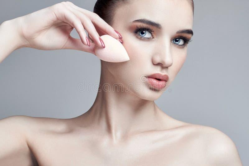 Vrouw met een sponsmake-up wordt toegepast op het gezicht dat Professionele mak stock foto