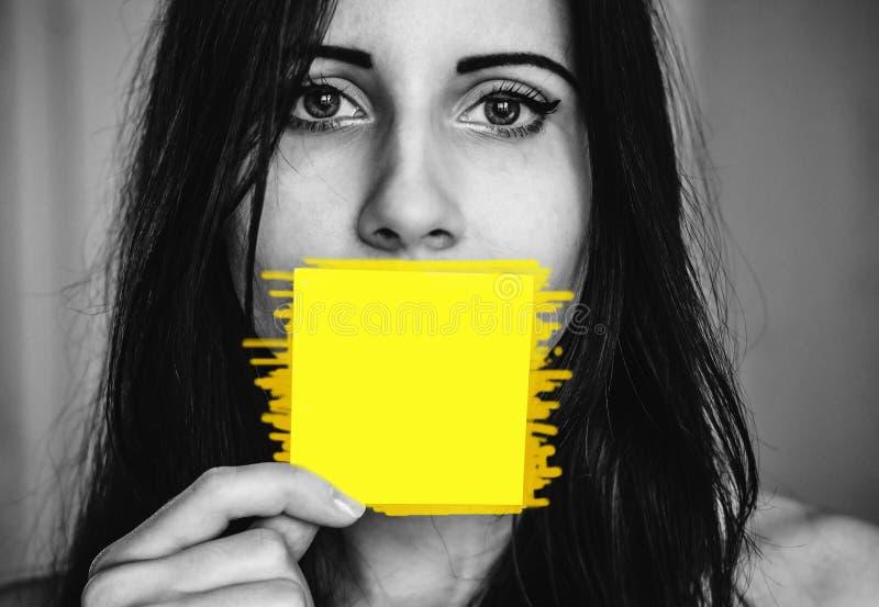 Vrouw met een sticker bij haar mond als een concept van vrouwenrechten en de noodzaak om daarover te praten en te schrijven royalty-vrije stock fotografie