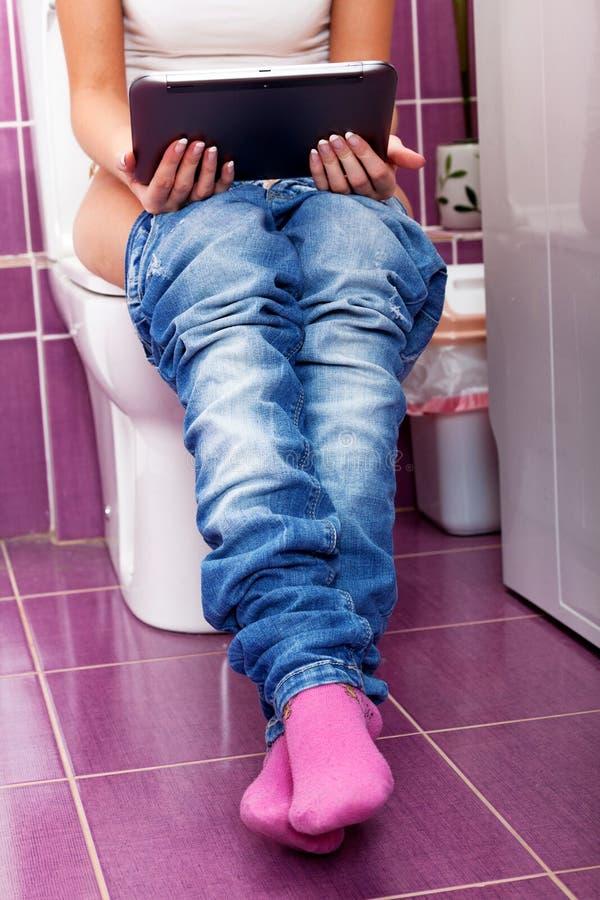 Vrouw met een tabletpc in een toilet stock foto