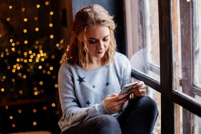 Vrouw met een telefoon door het venster stock foto's